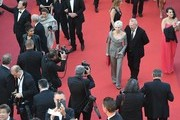 """French director Tonie Marshall (C) and French fashion designer Jean-Paul Gaultier (C-R) pose as they arrive on May 15, 2016 for the screening of the film """"Mal de Pierres (From the Land of the Moon)"""" at the 69th Cannes Film Festival in Cannes, southern France.  / AFP / Antonin THUILLIER"""