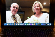 Larry Wood (L) and Gay Wood of Texas are shown on a laptop screen using the Zoom videoconferencing software before their Elvis Presley-themed, live wedding vow renewal ceremony to celebrate their 50th anniversary amid the spread of the coronavirus (COVID-19) at Graceland Wedding Chapel on July 28, 2020 in Las Vegas, Nevada. The chapel, which originated Elvis-themed weddings in 1977, is currently open for in-person weddings with groups of up to 20 people in the same party. It is now offering the world's first virtual Elvis-themed vow renewal and commitment ceremonies for people all over the world who are unable to travel to Las Vegas or otherwise appear in person because of the pandemic. Couples can invite up to 100 guests to watch their ceremony live via Zoom.