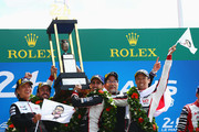 The Toyota Gazoo Racing TS050 Hybrid team of Fernando Alonso, Sebastien Buemi and Kazuki Nakajima celebrate alongside Shigeki Tomoyama (L) and Hisatake Murata (2R) of Toyota Gazoo Racing after they win for the first time at the Le Mans 24 Hour race at the Circuit de la Sarthe on June 17, 2018 in Le Mans, France.