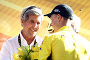 Chris Froome of Great Britain and Team SKY chats to American politican John Kerry on the podium after stage fifteen of the 2017 Tour de France, a 189.5km road stage from Laissac-Severac I'Eglise to Le Puy-en-Velay, on July 16, 2017 in Le Puy-en-Velay, France.
