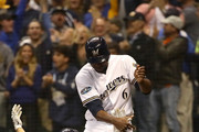 Ryan Braun #8 of the Milwaukee Brewers celebrates with Lorenzo Cain #6 after scoring a run off of a double hit by Jesus Aguilar #24 of the Milwaukee Brewers during the first inning in Game Six of the National League Championship Series at Miller Park on October 19, 2018 in Milwaukee, Wisconsin.