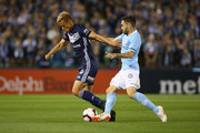 Keisuke Honda of the Victory and Anthony Caceres of Melbourne City compete for the ball during the round one A-League match between Melbourne Victory and Melbourne City at Marvel Stadium on October 20, 2018 in Melbourne, Australia.