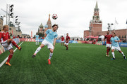 """Marina Fedorova (L) and  Diego Forlan (C) compete during the Legends Football Match in """"The park of Soccer and rest"""" at Red Square on July 11, 2018 in Moscow, Russia."""