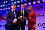 Geoff Shreeves (L) and Rachel Riley (R)present the award to Robin van Persie (C) during the 21st Legends of football event to celebrate 25 seasons of the Premier League and raise money for music therapy charity Nordoff Robbins at The Grosvenor House Hotel