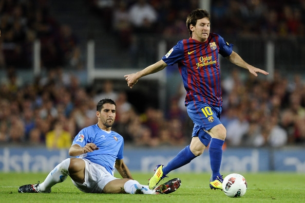 Lionel Messi Lionel Messi of FC Barcelona (R) duels for the ball with Raul Garcia Escudero of CA Osasuna during the La Liga soccer match between FC Barcelona and CA Osasuna at Camp Nou Stadium on September 17, 2011 in Barcelona, Spain.