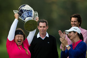 Lorena Ochoa of Mexico (blue sweater) presents Christina Kim of the United States with the champion's trophy following the 2014 Lorena Ochoa Invitational presented by Banamex at Club de Golf Mexico on November 16, 2014 in Mexico City, Mexico.