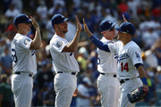 (L-R) Ross Stripling #68, Rich Hill #44, Chase Utley #26 and Enrique 'Kike' Hernandez #14 of the Los Angeles Dodgers celebrate with high-fives after the MLB game against the Los Angeles Angels of Anaheim at Dodger Stadium on July 15, 2018 in Los Angeles, California. The Dodgers defeated the Angels 5-3.