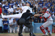 Homeplate umpire David Rackley #86 calls Chase Utley #26 of the Los Angeles Dodgers safe at the plate as catcher Martin Maldonado #12 of the Los Angeles Angels of Anaheim protests and holds up his glove to Rackley in the ninth inning of their MLB game at Dodger Stadium on July 14, 2018 in Los Angeles, California. Calhoun's solo homerun was the eventual game-winning run. The Angels defeated the Dodgers 5-4.