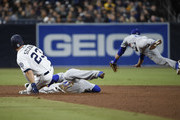 Matt Szczur #23 of the San Diego Padres gets to second base as Corey Seager #5, center, and Chase Utley #26 dive for the throw during the sixth inning of a baseball game at PETCO Park on April 17, 2018 in San Diego, California.