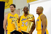Kobe Bryant #24  of the Los Angeles Lakers smiles as he holds two NBA Finals Larry O'Brien Championship Trophy's as he poses for a photograph with teammates Pau Gasol #16 and Derek Fisher #2 during Media Day at the Toyota Center on September 25, 2010 in El Segundo, California. NOTE TO USER: User expressly acknowledges and agrees that, by downloading and/or using this Photograph, user is consenting to the terms and conditions of the Getty Images License Agreement.