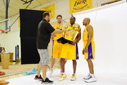 Photographer Noah Graham gives Kobe Bryant #24 of the Los Angeles Lakers two NBA Finals Larry O'Brien Championship Trophy's during a photo session with teammates Pau Gasol #16 (L) and Derek Fisher #2 during Media Day at the Toyota Center on September 25, 2010 in El Segundo, California. NOTE TO USER: User expressly acknowledges and agrees that, by downloading and/or using this Photograph, user is consenting to the terms and conditions of the Getty Images License Agreement.