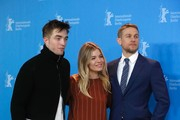 """(L-R) British actor Robert Pattinson, US actress Sienna Miller and British actor Charlie Hunnam pose for photographers during a photocall for the film """"The Lost City of Z"""" presented at the Berlinale Special section of the 67th Berlinale film festival in Berlin on February 14, 2017. / AFP / Odd ANDERSEN"""