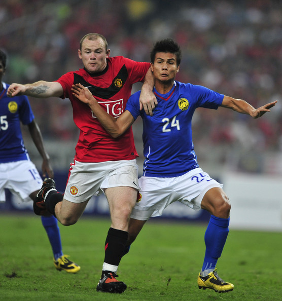 Wayne Rooney Wayne Rooney of Manchester United (L) clashes with Mohd Muslim Ahmad of Malaysia XI during the pre-season friendly match between Manchester United and Malaysia XI at Bukit Jalil National Stadium on July 20, 2009 in Kuala Lumpur, Malaysia.