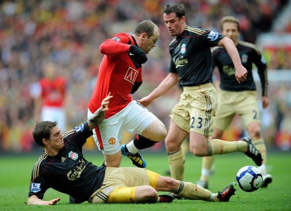 Wayne Rooney (C) of Manchester United is challenged by Daniel Agger (L) and