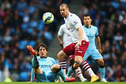 David Silva of Manchester City is challenged by Ron Vlaar of Aston Villa during the Barclays Premier League match between Manchester City and Aston Villa at Etihad Stadium on April 25, 2015 in Manchester, England.