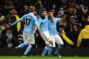 (R-L) Sergio Aguero of Manchester City is congratulated by teammates David Silva and Kevin De Bruyne of Manchester City after scoring his team's third goal during the Capital One Cup Semi Final, second leg match between Manchester City and Everton at the Etihad Stadium on January 27, 2016 in Manchester, England.