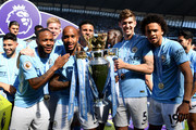 Raheem Sterling of Manchester City, Kevin De Bruyne of Manchester City, Fabian Delph of Manchester City, Kyle Walker of Manchester City, John Stones of Manchester City and Leroy Sane of Manchester City celebrate with The Premier League Trophy after the Premier League match between Manchester City and Huddersfield Town at Etihad Stadium on May 6, 2018 in Manchester, England.