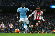 Steven Fletcher of Sunderland directs a header on goal under pressure from Bacary Sagna of Manchester City during the Barclays Premier League match between Manchester City and Sunderland at the Etihad Stadium on December 26, 2015 in Manchester, England.