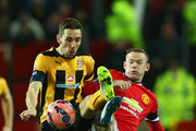 Tom Champion of Cambridge United and Wayne Rooney of Manchester United battle for the ball during the FA Cup Fourth round replay match between Manchester United and Cambridge United at Old Trafford on February 3, 2015 in Manchester, England.