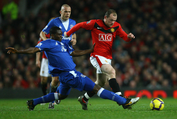 Joseph Yobo of Everton challenges Wayne Rooney of Manchester United during the Barclays Premier League match between Manchester United and Everton at Old Trafford on November 21, 2009 in Manchester, England.