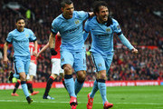 Sergio Aguero of Manchester City (C) celebrates with David Silva (R) and team mates as he scores their first goal during the Barclays Premier League match between Manchester United and Manchester City at Old Trafford on April 12, 2015 in Manchester, England.