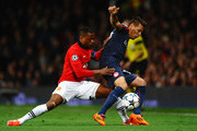 Patrice Evra of Manchester United competes with Hernan Perez of Olympiacos during the UEFA Champions League Round of 16 second round match between Manchester United and Olympiacos FC at Old Trafford on March 19, 2014 in Manchester, England.