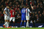 Gareth McAuley (1st L, obscured) of West Bromwich Albion is shown a red card by referee Mike Dean (1st R) during the Barclays Premier League match between Manchester United and West Bromwich Albion at Old Trafford on November 7, 2015 in Manchester, England.
