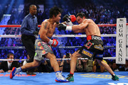 (L-R) Manny Pacquiao throws a left at Juan Manuel Marquez during their welterweight bout at the MGM Grand Garden Arena on December 8, 2012 in Las Vegas, Nevada.