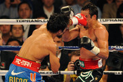 (L-R) Manny Pacquiao throws a left to the head of Juan Manuel Marquez during the WBO world welterweight title fight at the MGM Grand Garden Arena on November 12, 2011 in Las Vegas, Nevada.