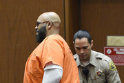 """Marion """"Suge"""" Knight escorted by Los Angeles Sheriff Deputy appears for a hearing at the Clara Shortridge Foltz Criminal Justice Center March 9, 2015 in Los Angeles, California.  The hearing was scheduled to determine if the two criminal cases against Knight, one for murder and attempted murder when Knight allegedly ran over two men in a Compton parking lot after an argument and another case involving an alleged robbery and criminal threats to a photographer in Beverly Hills, should be moved to the downtown Los Angeles courthouse."""