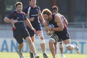 Scott Higginbotham of the Rebels runs with the ball as Nic Henderson and Ged Robinson look on during a Melbourne Rebels Super Rugby Training Session at Visy Park on May 21, 2013 in Melbourne, Australia.