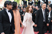"""(L-R) Jeong Jinyoung, Kim Minheet, Isabelle Hupert and director Hong SangSoo of  'Claire's Camera (Keul-Le-Eo-Ui-Ka-Me-La)' walk the red carpet ahead of the """"The Meyerowitz Stories"""" screening during the 70th annual Cannes Film Festival at Palais des Festivals on May 21, 2017 in Cannes, France."""