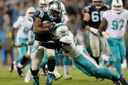 Reshad Jones #20 of the Miami Dolphins tries to stop Jonathan Stewart #28 of the Carolina Panthers during their game at Bank of America Stadium on November 13, 2017 in Charlotte, North Carolina.