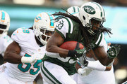 Chris Ivory #33 of the New York Jets runs with the ball as  Koa Misi #55 of the Miami Dolphins trails during their game at MetLife Stadium on December 1, 2013 in East Rutherford, New Jersey.