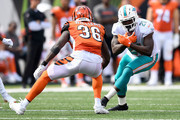 Frank Gore #21 of the Miami Dolphins attempts to run the ball past Shawn Williams #36 of the Cincinnati Bengals during the third quarter at Paul Brown Stadium on October 7, 2018 in Cincinnati, Ohio.