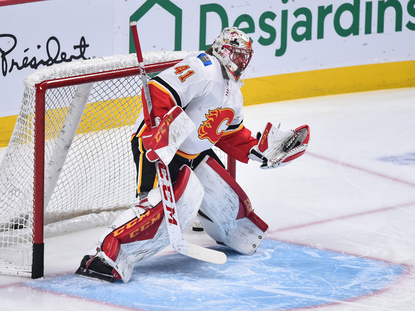 Calgary Flames vs. Montreal Canadiens [player,college ice hockey,ice hockey position,sports,goaltender,ice hockey,hockey protective equipment,sports gear,team sport,hockey,mike smith,gloves,puck,warm-up,canada,bell centre,montreal canadiens,calgary flames,nhl,game]