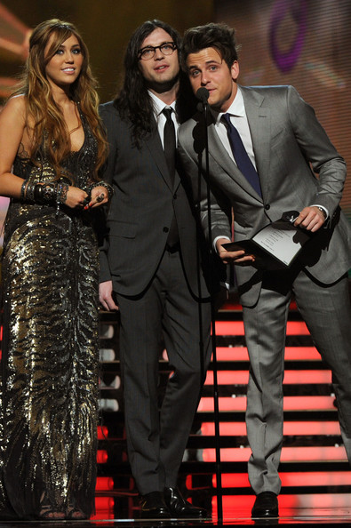 Miley Cyrus Singer Miley Cyrus, musician Nathan Followill and musician Jared Followill of Kings of Leon speak onstage during The 53rd Annual GRAMMY Awards held at Staples Center on February 13, 2011 in Los Angeles, California.