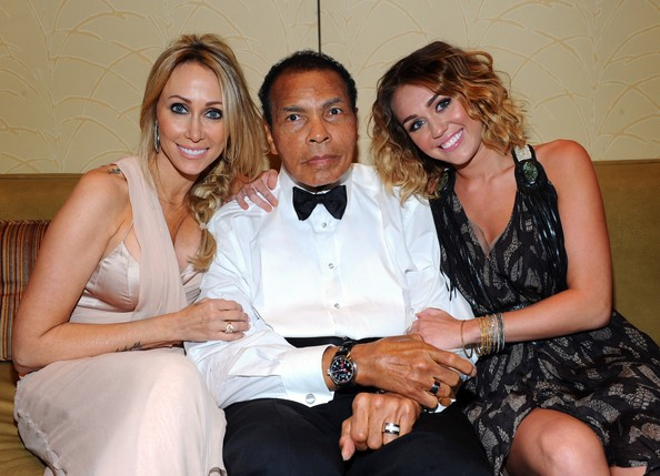Miley Cyrus Tish Cyrus, Muhammad Ali, and singer Miley Cyrus pose backstage during Muhammad Ali's Celebrity Fight Night XIII held at JW Marriott Desert Ridge Resort & Spa on March 24, 2012 in Phoenix, Arizona.