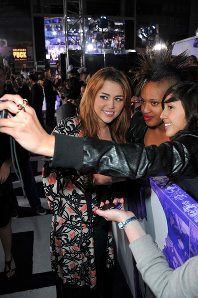 """Miley Cyrus Singer Miley Cyrus poses with a fan as he arrives at the premiere of Paramount Pictures' """"Justin Bieber: Never Say Never"""" held at Nokia Theater L.A. Live on February 8, 2011 in Los Angeles, California."""