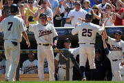 Joe Mauer #7, Luke Hughes #38, Jim Thome #25 and Jason Repko #18 of the Minnesota Twins celebrate the Twins taking the lead in the seventh inning against the Milwaukee Brewers on July 3, 2011 at Target Field in Minneapolis, Minnesota. The Twins defeated the Brewers 9-7.