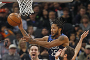 Derrick Rose #25 of the Minnesota Timberwolves grabs a rebound in front of Marco Belinelli #18 of the San Antonio Spurs  in season opener at AT&T Center on October 17 , 2018  in San Antonio, Texas.  NOTE TO USER: User expressly acknowledges and agrees that , by downloading and or using this photograph, User is consenting to the terms and conditions of the Getty Images License Agreement.