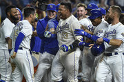 Salvador Perez #13 celebrates with Whit Merrifield #15 and members of the Kansas City Royals as he celebrates his walk-off grand slam against the Minnesota Twins in the ninth inning at Kauffman Stadium on September 14, 2018 in Kansas City, Missouri.