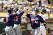 Josh Willingham #16 of the Minnesota Twins is congratulated by Chris Parmelee #27 and Kurt Suzuki #8 after he hit a two-run home run in the eighth inning of their game against the Oakland Athletics at O.co Coliseum on August 10, 2014 in Oakland, California.