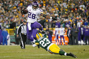 Adrian Peterson #28 of the Minnesota Vikings hurdles Damarious Randall #23 of the Green Bay Packers during the third quarter of their game at Lambeau Field on January 3, 2016 in Green Bay, Wisconsin.