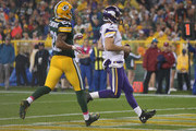 Quarterback Christian Ponder #7 of the Minnesota Vikings scrambles up the middle for a 6 yard touchdown against the Green Bay Packers in the forth quarter at Lambeau Field on October 2, 2014 in Green Bay, Wisconsin.