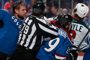 Linesman Kiel Murchison #79 seperates Jan Hejda #8 of the Colorado Avalanche and Nathan MacKinnon #29 of the Colorado Avalanche from Charlie Coyle #3 of the Minnesota Wild as they scuffle in the first period at Pepsi Center on February 28, 2015 in Denver, Colorado.