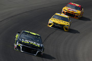 Jimmie Johnson, driver of the #48 Lowe's for Pros Chevrolet, leads Daniel Suarez, driver of the #19 Stanley Toyota, and Chris Buescher, driver of the #37 Slim Jim Chevrolet, during the Monster Energy NASCAR Cup Series Consmers Energy 400 at Michigan International Speedway on August 12, 2018 in Brooklyn, Michigan.