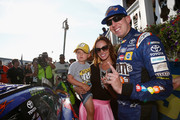 Kyle Busch, driver of the #18 M&M's Caramel Toyota, his wife, Samantha, and their son, Brexton, pose for a photo with the winner's decal on his car in Victory Lane after winning the Monster Energy NASCAR Cup Series Gander Outdoors 400 at Pocono Raceway on July 29, 2018 in Long Pond, Pennsylvania.