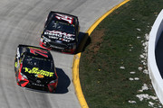 Martin Truex Jr., driver of the #78 5-hour ENERGY/Bass Pro Shops Toyota, leads Clint Bowyer, driver of the #14 Haas Automation Demo Day Ford, during the weather delayed Monster Energy NASCAR Cup Series STP 500 at Martinsville Speedway on March 26, 2018 in Martinsville, Virginia.