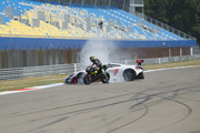 """Johann Zarco of France and Monster Yamaha Tech 3 rides the bike and makes a burn out in front of Bruno Senna of Brazil drives the car during the pre-event """"A race between a Yamaha M1 and a McLaren GT3"""" during the MotoGP Netherlands - Preview on June 22, 2017 in Assen, Netherlands."""